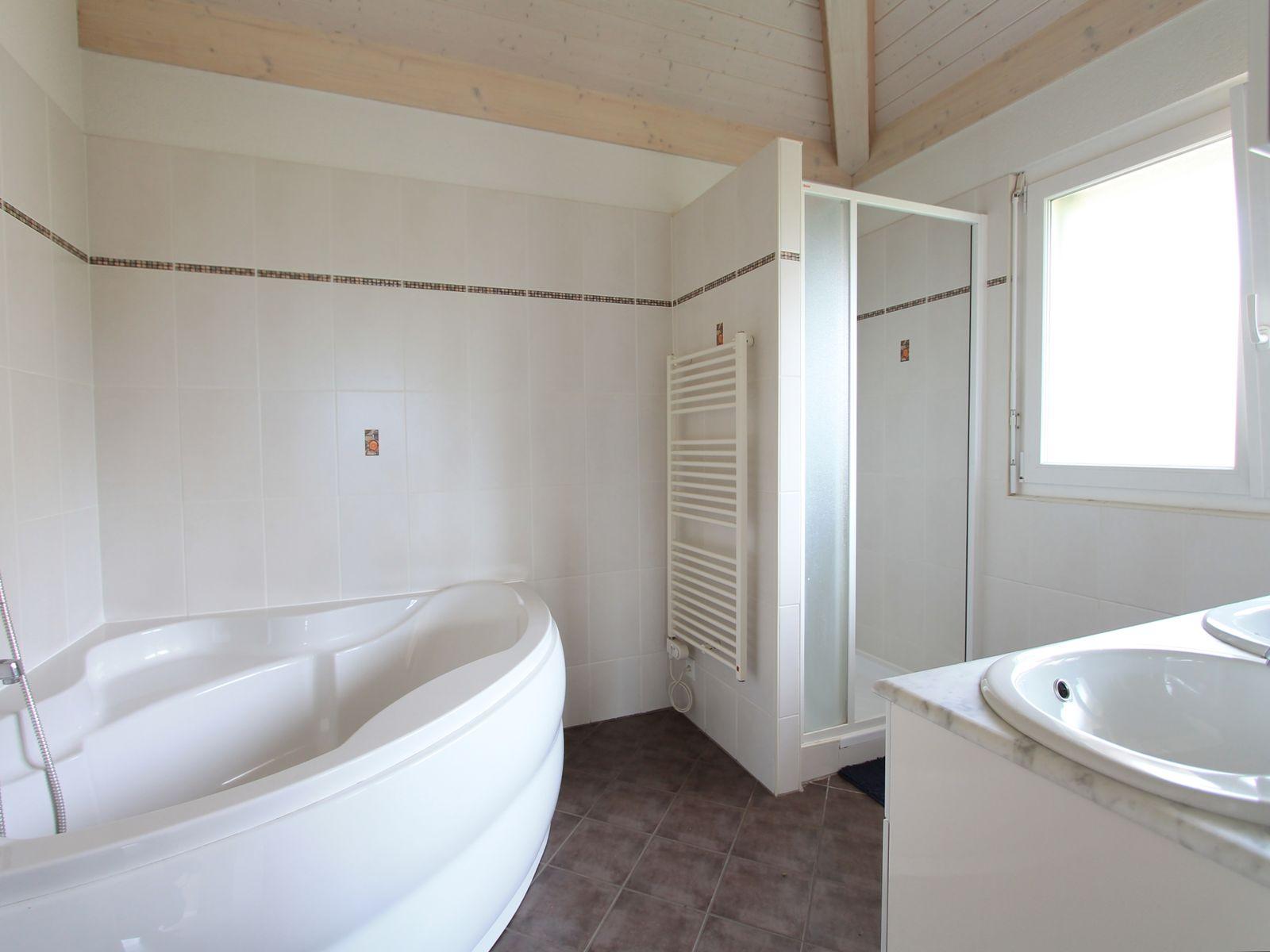 Salle-de-bains avec baignoire en coin, douche séparée et double lavabo