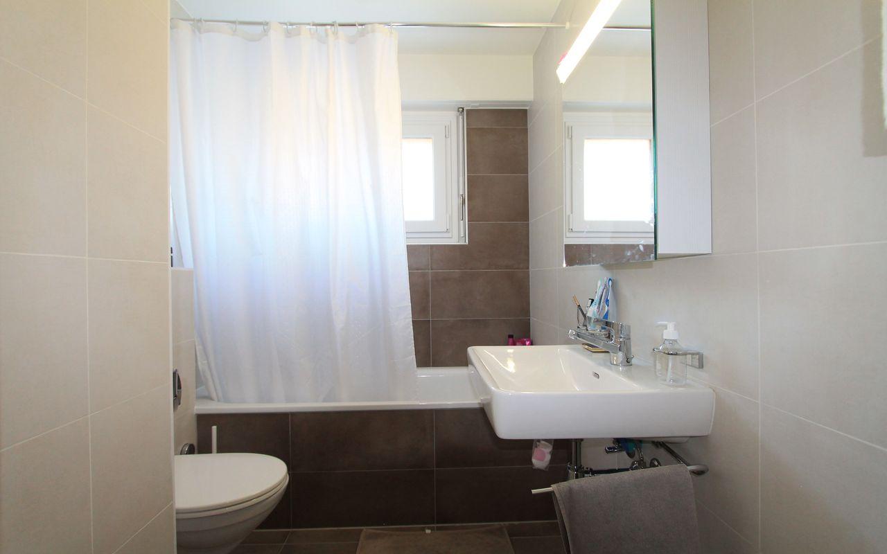 Salle-de-bains avec baignoire et fenêtre